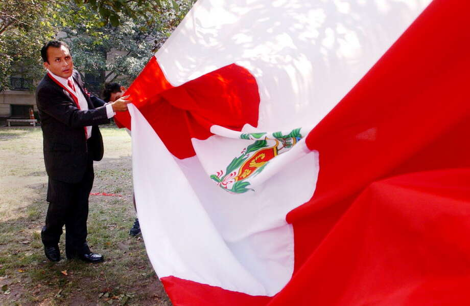 Stamford_072703_Lucas Romero of the Peruvian American Community Center folds a giant Peruvian flag before the start of a ceremony honoring the 182nd anniversary of the independence of the Republic of Peru. The ceremony was held at Heritage Park in Stamford, behind the Old Town Hall. Kerry Sherck/Staff photo Photo: Kerry Sherck / ST