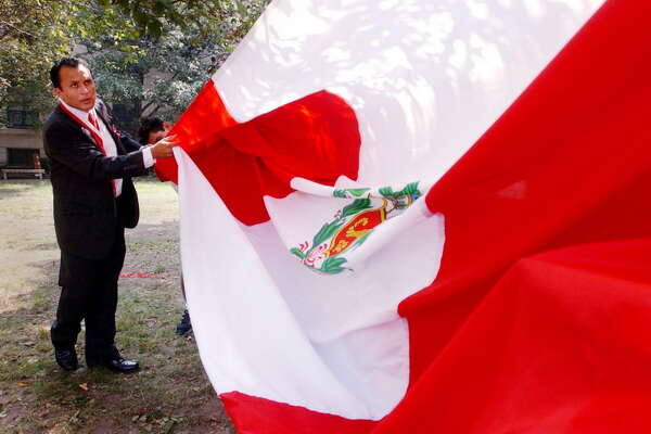 Stamford_072703_Lucas Romero of the Peruvian American Community Center folds a giant Peruvian flag before the start of a ceremony honoring the 182nd anniversary of the independence of the Republic of Peru. The ceremony was held at Heritage Park in Stamford, behind the Old Town Hall. Kerry Sherck/Staff photo
