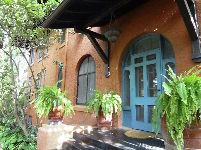 Architect Ted Flato moved the main entrance to his home in Alamo Heights from the front to the side and made it accessible by several steps. The 1909 home, in a rusty terracotta red, is a combination of styles, including Andalucian, Morrocan and Craftsman.
