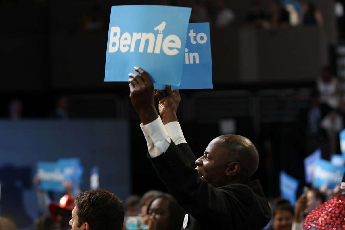 With two Bernie signs in hand, one attendee watches Sen. Bernie Sanders speack at the first night of the Democratic National Convention in Philadelphia on July 25, 2016.