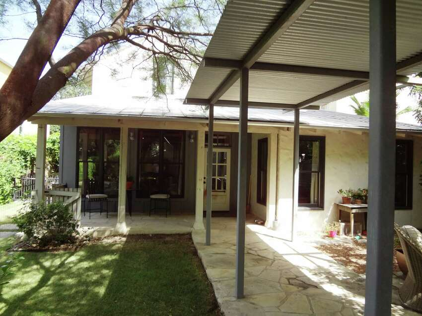 The back of the house has a covered walkway that leads past a cistern to a garage apartment.