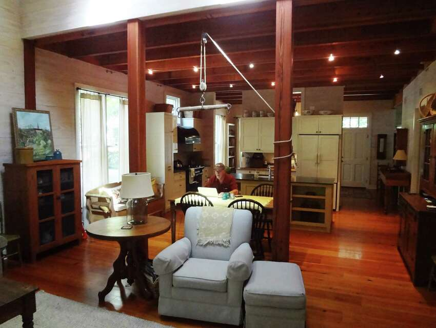 Exposed wood beams and longleaf pine floors warm up the downstairs rooms of Mickey Conrad's home.