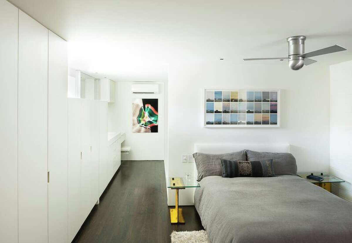 Tobin Smith designed the cabinet/closets along the wall, as well as the yellow I-beam end table, in the master bedroom.