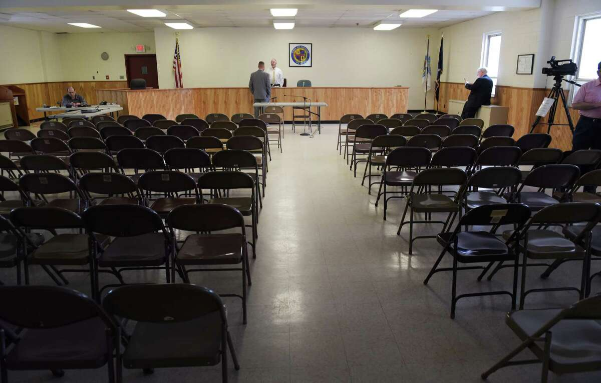 Graham Jesmer, background left, assistant counsel, State of New York Public Service Commission, and Administrative Law Judge Sean Mullany wait to see if anyone else will appear during a public hearing on the Department of Public Service plan to add a sibling to the 518 area code on Thursday, July 28, 2016, in Colonie, N.Y. Only a handful of people showed up to speak at the hearing. New numbers under the current 518 area code will likely run out in the first quarter of 2019, the Department of Public Service predicts. (Paul Buckowski / Times Union)