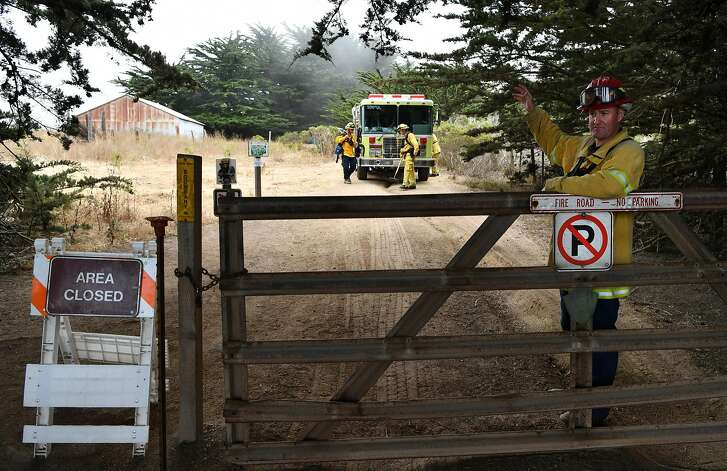 Tyler Mortensen (R) of Santa Clara County Fire Dept. blocks an entrance to Garrapata State Park near Carmel California on July 28, 2016. Scorching more than 27,000 acres, the Soberanes Fire has taken a toll on local businesses and caused multiple closures at state parks.