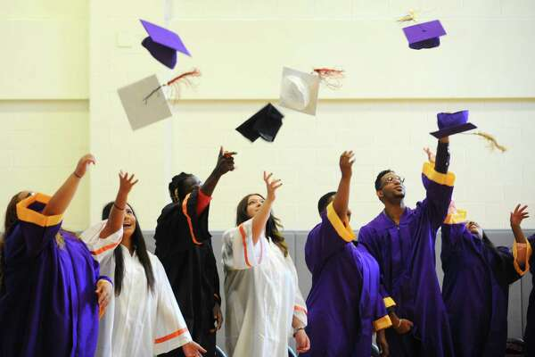 Westhill and Stamford High students throw their caps during the summer school graduation held at Stamford High School on Thursday, July 28, 2016.