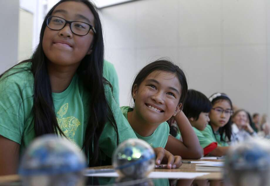Audrey Thiphadong (left), 12, and Trinity Nguyen, 10, listen to instructions on how to write simple code during the class at the Apple Store on Union Square. Photo: Paul Chinn, The Chronicle