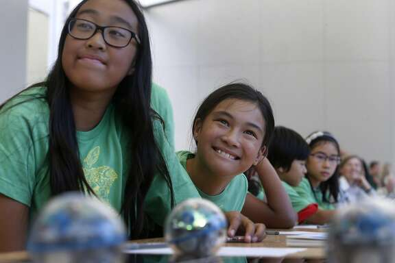 Audrey Thiphadong (left), 12, and Trinity Nguyen, 10, learn how to program and control a Sphero robotic ball at an Apple youth coding class in San Francisco, Calif. on Thursday, July 28, 2016.