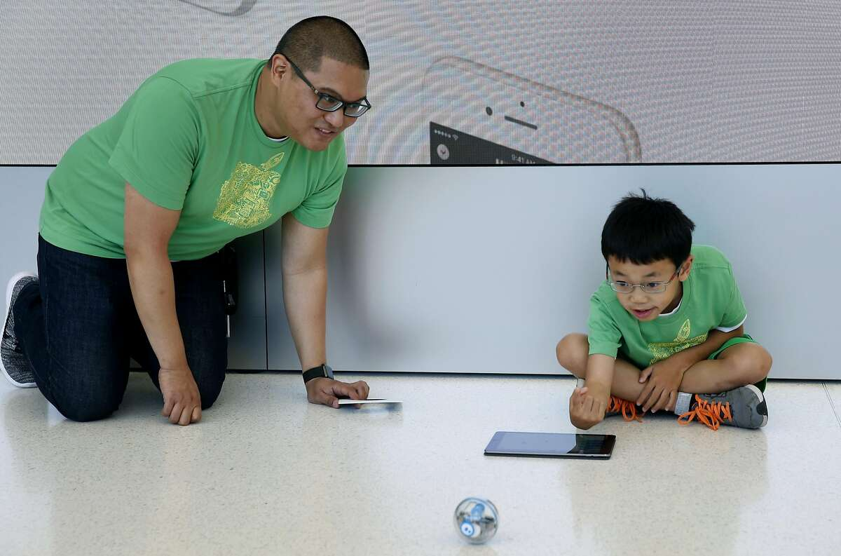 Alvin Viray encourages Tom Lee, 9, while he learns how to program and control a Sphero robotic ball at an Apple youth coding class in San Francisco, Calif. on Thursday, July 28, 2016.