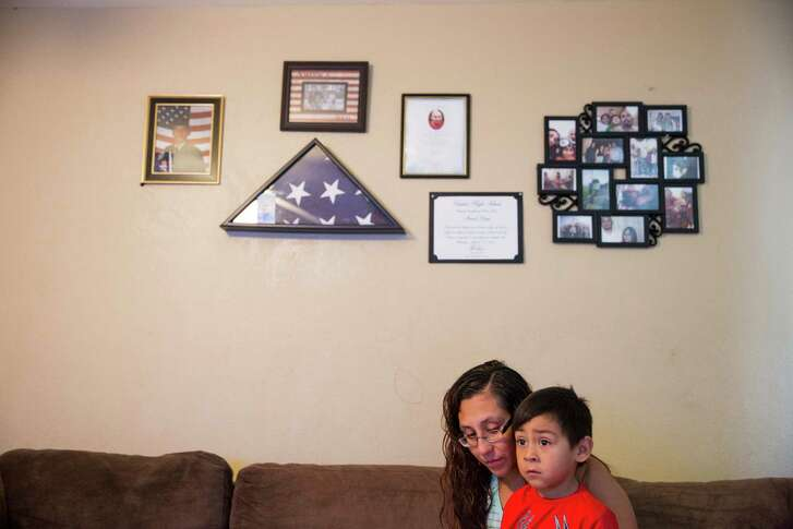 "Sara Mata holds her son Jeremiah Garcia, 4, on the couch at their home in Laredo, Texas on July 26, 2016.  Above them hang reminders of Mata's husband, Manuel Garza, who was a veteran who committed suicide in the Fall of 2015 after struggling with PTSD from doing two tours in Iraq.  ""He was everything I never thought I could have,"" Sara Mata said."