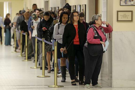 FILE - In this Tuesday, June 7, 2016 file photo, voters wait to cast ballots at City Hall in San Francisco. Voter turnout in California's primary looked about average, despite a last-minute surge in registration and intense interest in an unusually competitive presidential contest. Ballots counted by Wednesday morning, June 8, represented only one in four eligible Californians and one in three registered voters. (AP Photo/Jeff Chiu, File)