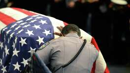 A Baton Rouge, La., police officer kneels at the casket of Police Cpl. Montrell Jackson, one of three officers killed in a shooting July 24. In the wake of such shootings, readers express their support for police in San Antonio.