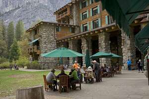 FILE - In this Oct. 24, 2015 file photo, people dine outside the Ahwahnee hotel in Yosemite National Park, Calif. The National Park Service has asked a federal trademark board to cancel trademarks, including the Ahwahnee hotel, obtained by Delaware North, the company that previously ran the park's hotels, restaurants and outdoor activities, the Sacramento Bee reported Friday, March 18, 2016. Delaware North, is demanding the park service pay it $51 million for the names and other intellectual property and has filed a lawsuit in federal court. (AP Photo/Ben Margot, File)