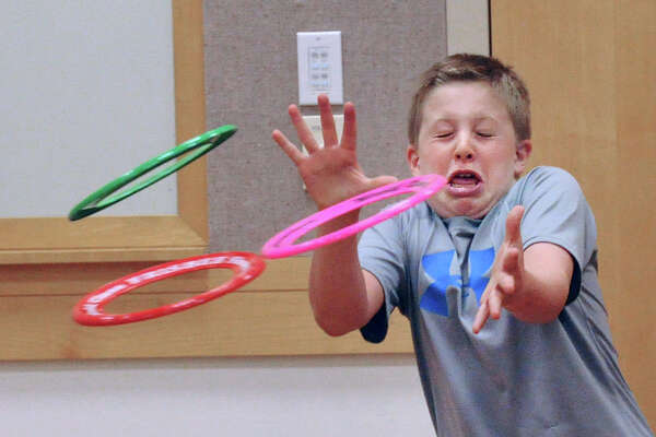 Ryan Brush, 12, of Greenwich, closes his eyes while attempting to catch five Frisbees (only three are shown) during a Frisbee clinic put on by Todd Brodeur a two-time Freestyle Frisbee Champion, in the meeting room at Greenwich Library, Conn., Thursday, July 28, 2016. Brush was attempting to catch the Frisbees thrown at him by Brodeur of Bellingham, Mass., who bills himself as a Frisbee educator and entertainer. Brodeur said that he has been playing Frisbee since his third-grade teacher, Mrs. Nelson, at the Allen Avenue School in North Attleborough, Mass., give him a Frisbee that he couldn't stop playing with and let him keep it.