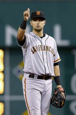 San Francisco Giants second baseman Joe Panik gives signals to the infield as the Pittsburgh Pirates bat in the ninth inning of a baseball game, Wednesday, June 22, 2016, in Pittsburgh.Panik drove in the go-ahead run in the sixth inning to lead the Giants to a 7-6 win. (AP Photo/Keith Srakocic)