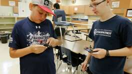 Sixth-grader Eirik Marquez (left)(ck), and Roosevelt High School junior Caleb Merkel repair a drone as 18 NEISD middle and high school students attend Drone Camp where students build and program their own drones.  On Thursday, July 28, 2016, the last day of camp, students flew their drones through a makeshift obstacle course at Roosevelt High School. The students consisted of middle and high school NEISD students. Many attend Ed White Middle School and Roosevelt High School's magnet programs: Design and Technology Academy (DATA) and Engineering and Technology Academy (ETA).  Sponsor CoDrone just got off Kickstarter and the district was one of the first in the country to host a camp according to the official press release. (Kin Man Hui/San Antonio Express-News)