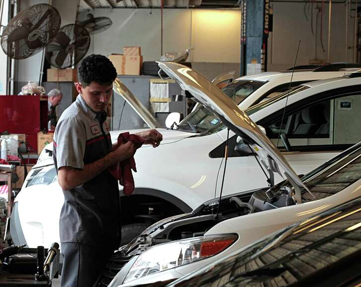 Sterling McCall Toyota technician Nilson Rivera checks a vehicle's oil level.  Group 1 anticipates continued revenue growth for the rest of the year in the U.S.