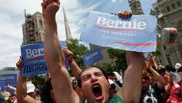 Supporters of Sen. Bernie Sanders, I-Vt., yell during a rally near City Hall in Philadelphia during the second day of the Democratic National Convention. Most Sanders supporters are backing Hillary Clinton, but a few sought Sanders' spotlight to continue their own mission.
