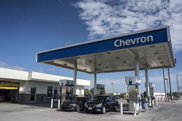 Vehicles refuel at a Chevron Corp. gas station in Albuquerque, New Mexico, U.S., on Tuesday, July 26, 2016. Chevron is scheduled to release earnings figures on July 29. Photographer: Sergio Flores/Bloomberg