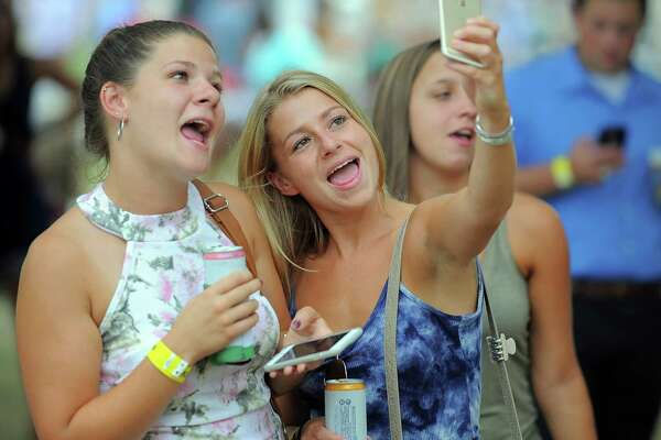 Rebecca LaPierre of Stratford, Conn. takes a selfie with her sister Danielle LaPierre as they wait for Eric Hutchison and his band The Believers to take the stage during the Alive@Five concert series in Stamford, Conn. on Thursday, July 28, 2016.