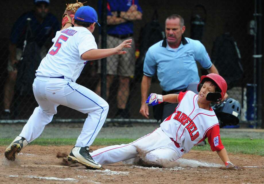 Fairfield American's Matt Vivona slides into home plate as Coginchaug's Jeremy Mangiameli tries to make the tag during Connecticut State Little League Championship action in Manchester, Conn. on Thursday July 28, 2016. Vivona was called safe. Fairfield American beat Coginchaug 6-2. Photo: Christian Abraham / Hearst Connecticut Media / Connecticut Post