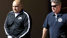 Ruben Reyes (left) is escorted Wednesday November 26, 2014 out of the Federal Courthouse in San Antonio, Texas. Reyes,36, is a purported enforcer for the Texas Mexican Mafia and was arrested on charges he killed three high-ranking members of the same gang and is also suspected of having given orders to kill Balcones Heights Police Officer Julian Pesina.