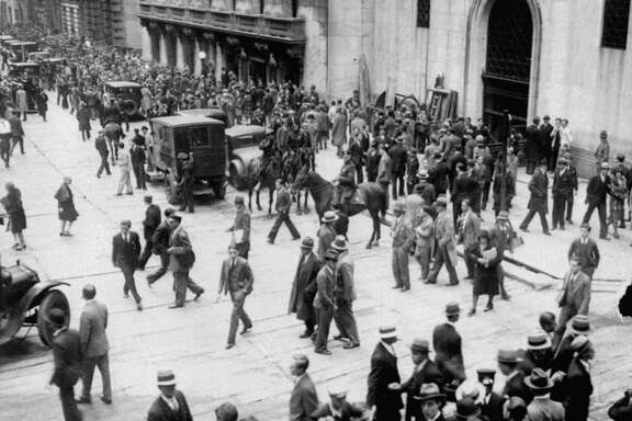 ADVANCE FOR TUESDAY, APRIL 18--Crowds move past the New York Stock Exchange, second building from right, on New York's Wall Street at the height of the stock market crash, Oct. 24, 1929, as policemen on horseback keep the throng moving. The history of the stock exchange is part of 'The Great Game: The Story of Wall Street,' a two-hour CNBC documentary premiering Monday, April 24, 2000.   (AP Photo)