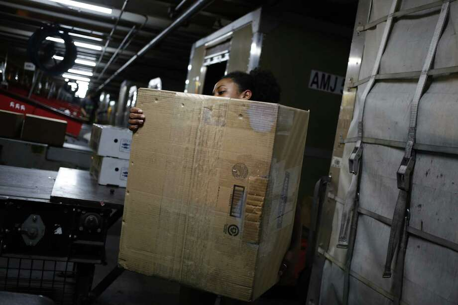 A worker unloads packages from a container during the night package sort at the United Parcel Service Inc. Worldport facility in Louisville, Kentucky. For the three months ended June 30, United Parcel Service Inc. earned $1.27 billion, or $1.43 per share. That compares with $1.23 billion, or $1.35 per share, a year earlier. Photo: Luke Sharrett /Bloomberg News / © 2016 Bloomberg Finance LP