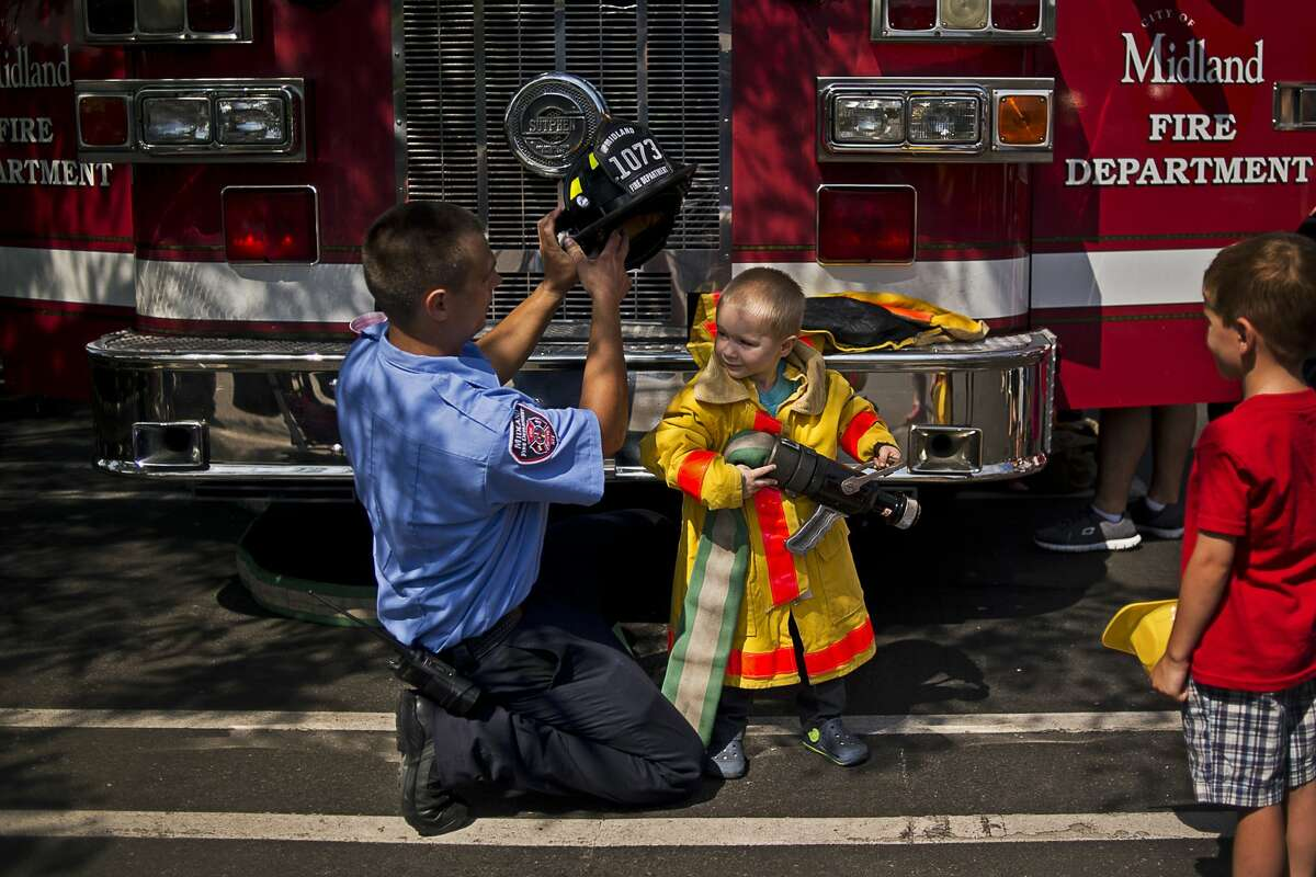 Midland firefighter Kevin Retzloff, left, helps Midland resident Jackson Mishler, 3, get suited up with firefighting gear on Thursday at Touch a Truck outside the Grace A. Dow Memorial Library in 2016.