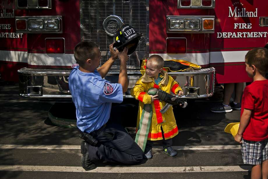 Midland firefighter Kevin Retzloff, left, helps Midland resident Jackson Mishler, 3, get suited up with firefighting gear on Thursday at Touch a Truck outside the Grace A. Dow Memorial Library. Over 15 trucks from construction crews to first responders were available for children to climb into and learn more about. Photo: Erin Kirkland/Midland Daily News/Erin Kirkland