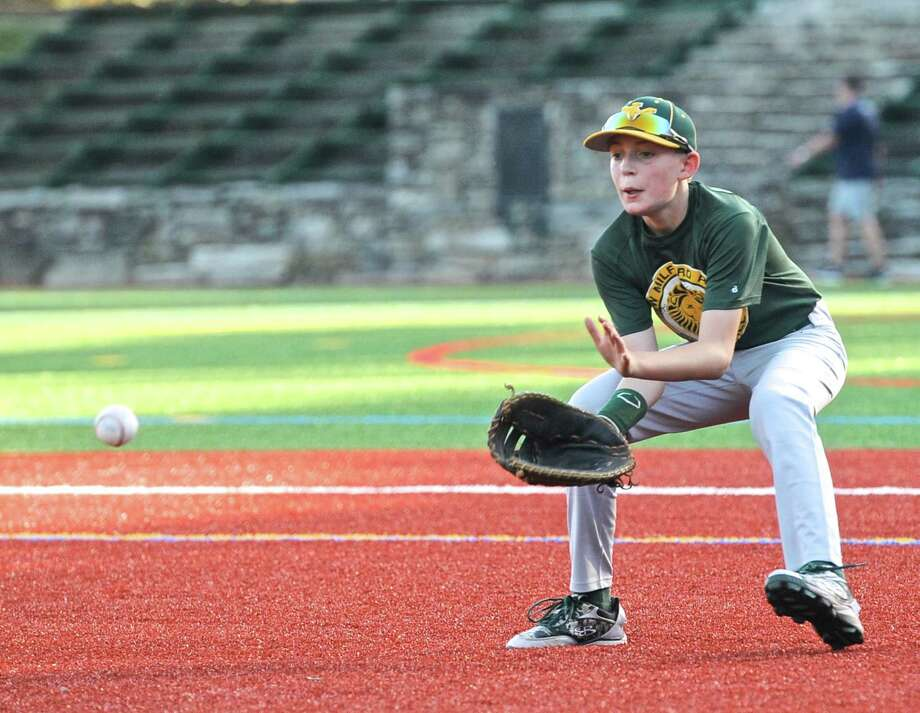New Milford's Justin LeClair fields a ground ball during a Cal Ripken 12/70 baseball team practice Wednesday at The Gunery School in Washington. The team will play in the Cal Ripken World Series beginning Saturday in Aberdeen, Md. Photo: H John Voorhees III / Hearst Connecticut Media / The News-Times