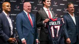 Texans quarterback Brock Osweiler stands with general manager Rick Smith (far left) owner Bob McNair and Cal McNair (far right) as he is introduced during a news conference at NRG Stadium on March 10, 2016, in Houston.