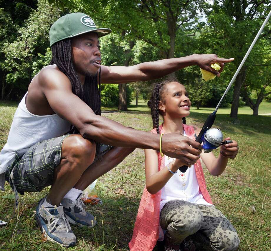 Danny Nelson of Schenectady and daughter Aisha, 7, watch their line baited with leftover hot wings in hopes of catching an alligator gar at Iroquois Lake in Central Park Friday July 29, 2016 in Schenectady, NY. Mayor McCarthy has put a $100 the alligator gar, an invasive fish that observers suspect has been killing the pond's fish.  (John Carl D'Annibale / Times Union) Photo: John Carl D'Annibale / 20037493A