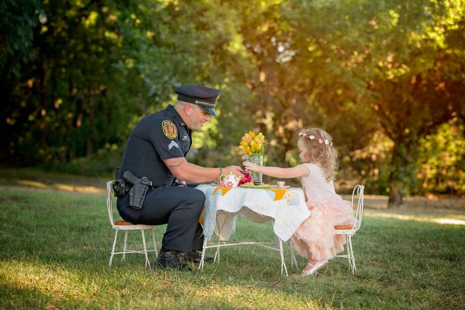 Cpl. Patrick Ray of the Rowlett Police Department has tea with Bexley Norvell, 2, on July 17, 2016, in Rowlett.Photographer Chelle Cates said the tea party photo shoot celebrated the first anniversary of Ray saving Bexley from choking on a small coin. Photo: Chelle Cates