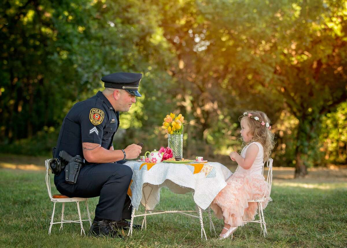 Cpl. Patrick Ray of the Rowlett Police Department has tea with Bexley Norvell, 2, on July 17, 2016, in Rowlett. Photographer Chelle Cates said the tea party photo shoot celebrated the first anniversary of Ray saving Bexley from choking on a small coin.