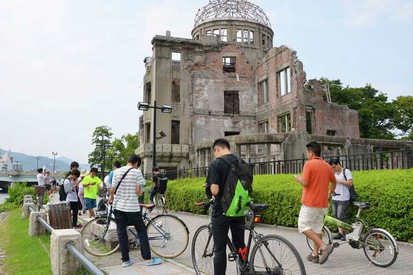 """In this July 26, 2016 photo, people play Pokemon Go near the Atomic Bomb Dome at Hiroshima Peace Memorial Park in Hiroshima, Japan. The creators of """"Pokemon Go"""" say they're working to remove real-world locations that don't wish to be included in the mobile gaming sensation."""