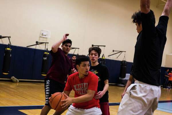 Damien Torres, 19, prepares to make a pass to his teammate while playing a game of pickup basketball at Centro Fitness in San Antonio.