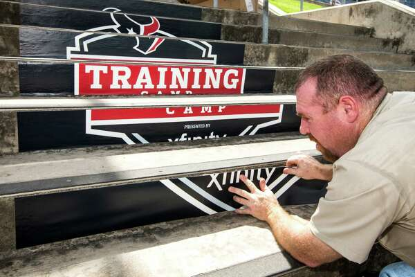 Bobby Lewis, of Signtex Imaging, works on placing logos on the stairway leading to the practice field while setting up the Methodist Training Center facility for Houston Texans Training Camp on Friday, July 29, 2016, in Houston. The Texans open training camp on Sunday.