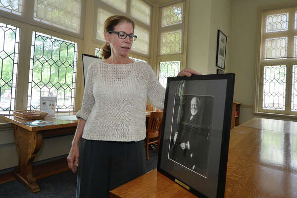 Norwalk Public Library Director Chris Bradley holds a portrait of Andrew Carnegie that hangs in the Carnegie room at the library. Norwalk has two Carnegie libraries, the main branch on Belden Avenue and the South Norwalk branch on Washington Street.
