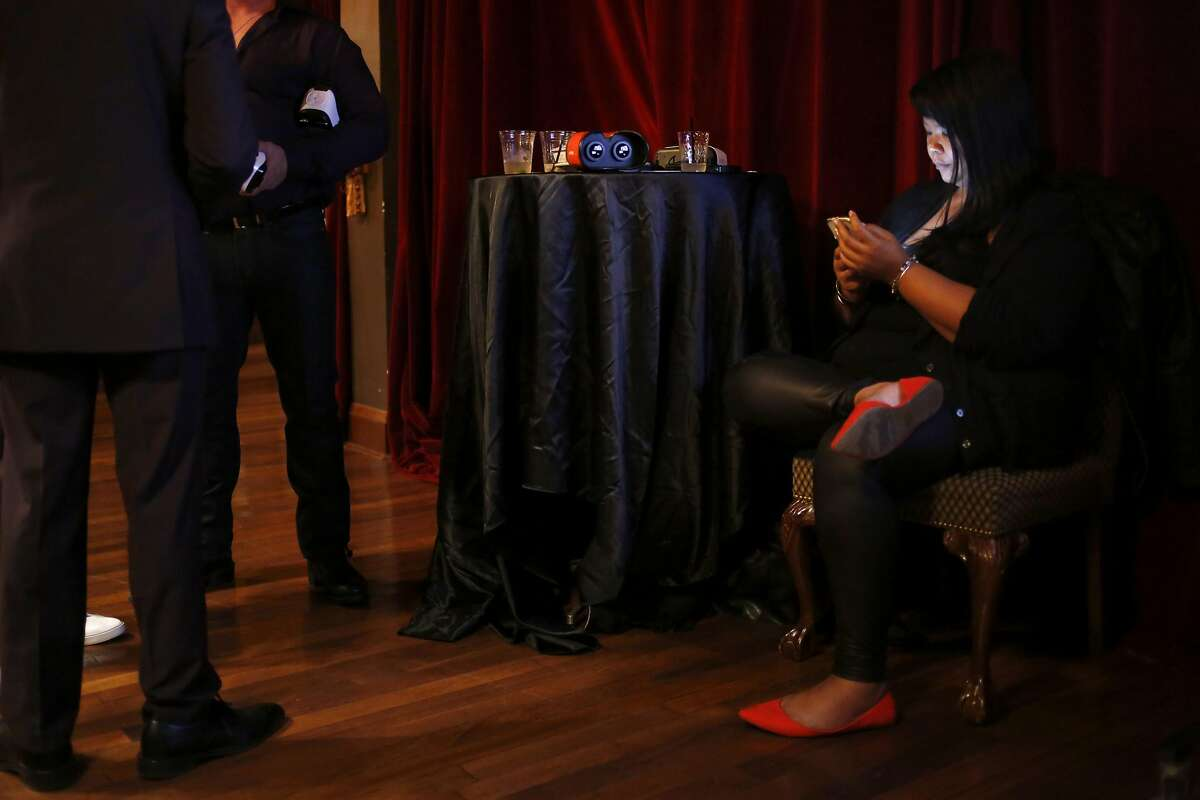 Anna Lee, president of Holofilms Productions, checks her phone beside a table with VR devices and half-empty drinks during a gathering of virtual reality pornography enthusiasts and businesses at Kink.com headquarters in San Francisco, California, on Thursday, July 28, 2016.
