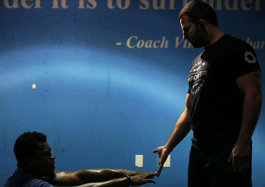 Dion Jordan, left, touches the hand of instructor Tareq Azim as he does sit-ups during a training session at Empower July 21, 2016 in San Francisco, Calif. Photo: Leah Millis, The Chronicle