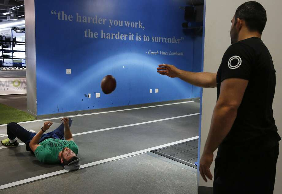 Tareq Azim, left, tosses a football to Cooper Helfet for him to practice blind catches during a training session at Empower July 21, 2016 in San Francisco, Calif. Photo: Leah Millis, The Chronicle