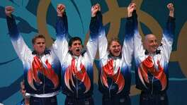 The United States 400-meter freestyle relay team celebrate winning the gold medal at the 1996 Summer Olympics in Atlanta on July 23, 1996. Seen from left to right are Gary Hall Jr., Bradley Schumacher, Josh Davis, and Jon Olsen.