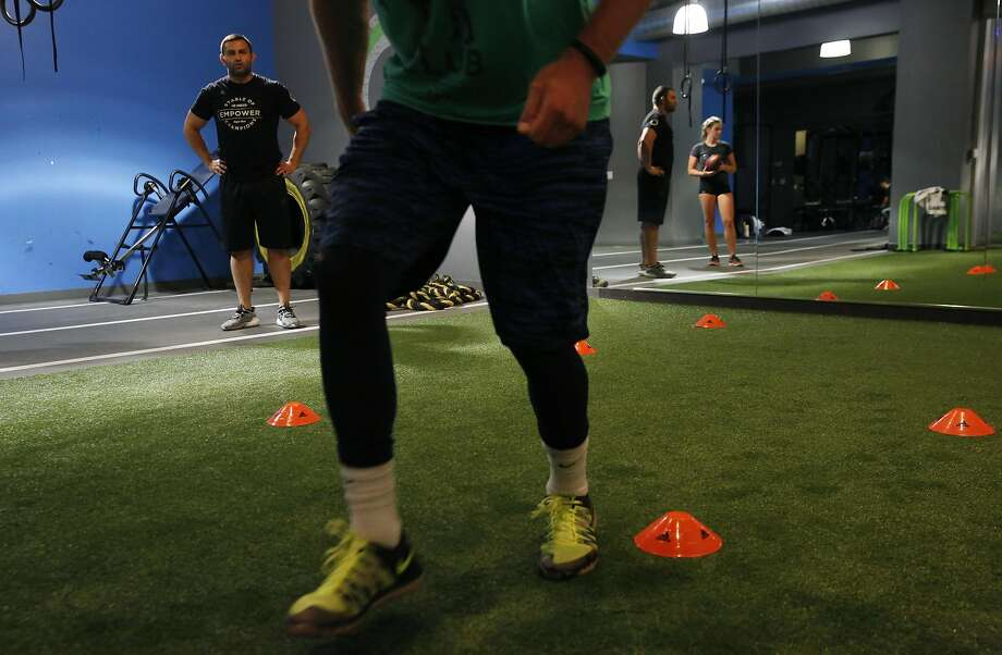 Trainer Tareq Azim (left) watches Cooper Helfet run through a drill during an exercise session at Azim's Empower gym in San Francisco. Photo: Leah Millis, The Chronicle
