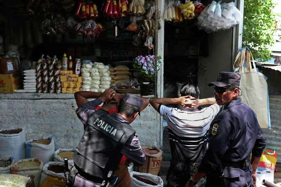 Members of the Policia Nacional Civil question young men at a market while on patrol with Salvadoran military personnel in the Colonia Jardin de Don Bosco of San Salvador, El Salvador. The neighborhood, like others in El Salvador, is home to two of the most powerful gangs in the country, MS-13 and Barrio 18. During their security detail, the soldiers will question young men and women to determine if they have a gang affiliation.