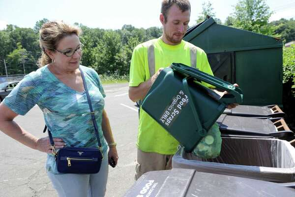 Pat O'Connor of Ridgefield, left, recycles her food scrapes at the Ridgefield Recycling Center, assisted by center attendant, Chris Foster, Thursday, July 28, 2016.