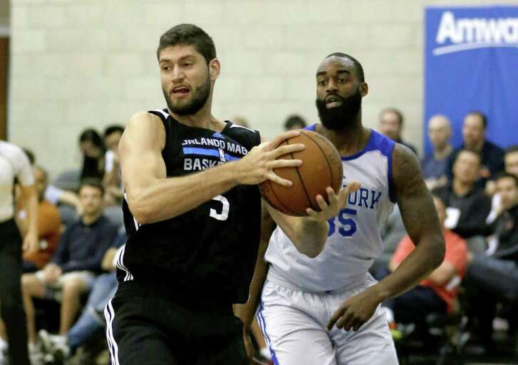 Orlando Magic White's Patricio Garino, grabs a rebound in front of New York Knicks' DaJuan Summers during the first half of an NBA summer league game on July 6, 2016, in Orlando, Fla.