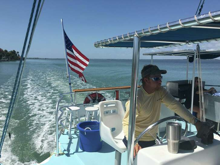 The captain of a catamaran snorkeling boat heads to the middle of the bay off of South Padre Island.