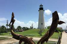 A wood carving of fish with the Port Isabel lighthouse in the backdrop.