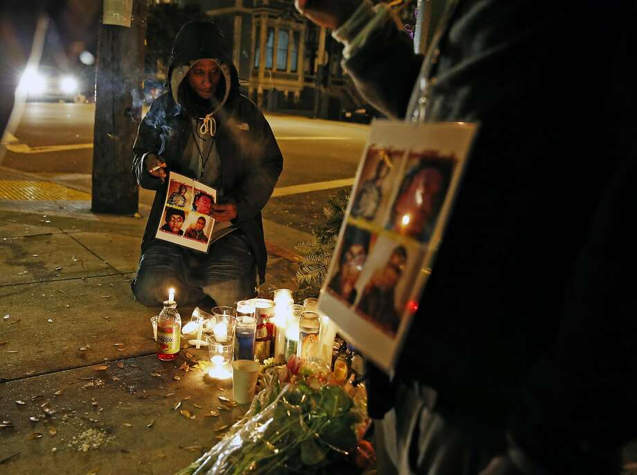 Daryis Mackey holds a photo montage of victims Yalani Chinyamurindi, David Saucier, Harith Atchan and Manuel O'Neal at a vigil last year. Photo: Scott Strazzante, The Chronicle